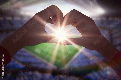 Composite image of woman making heart shape with hands