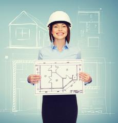 smiling businesswoman in helmet showing blueprint