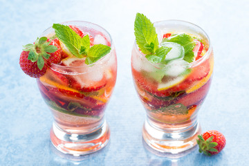 cocktail with fresh strawberries and citrus in glasses