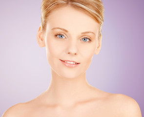 beautiful young woman face over violet background