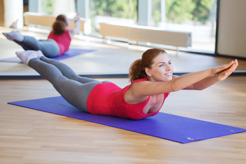 smiling woman doing exercise on mat in gym