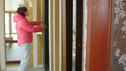 Customer chooses inner wooden door in doors store showroom