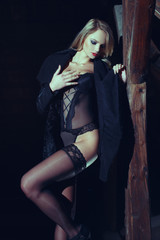 Sensual blonde woman posing in underwear at night in barn