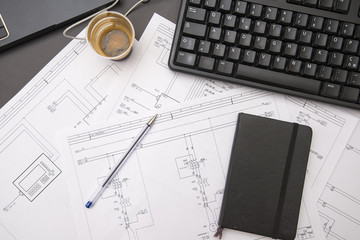 Drawing of electrical circuits on engineer desk with coffee