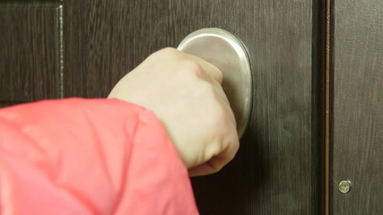Female hand with key locking or unlocking the front door