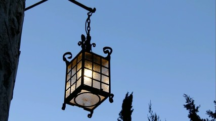 old lantern on a stone wall swinging in the wind