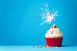 Leinwanddruck Bild - Cupcake with sparkler on blue