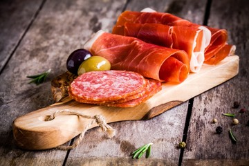 slices of prosciutto with salami, olives and rosemary
