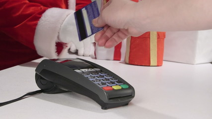 Santa Claus customer paying to shop assistant by credit card