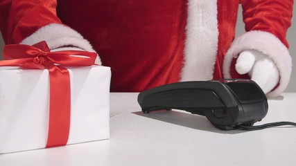 Santa Claus behind the counter using credit card reader