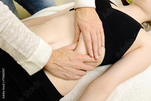 Leinwanddruck Bild Heilpraktiker behandelt Bauch mit Osteopathie