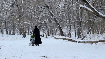 Woman with Baby Stroller on Snowy Park