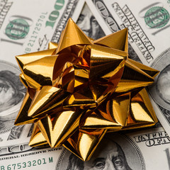 One hundred US dollars bills with holidays bow