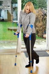 Frau mit Gehbehinderung geht an Krücken