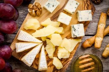Camembert cheese, blue cheese closeup, bread sticks, grapes