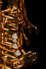 Fragment of a saxophone on a black background