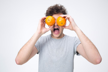 Surprised man looking through oranges over gray background