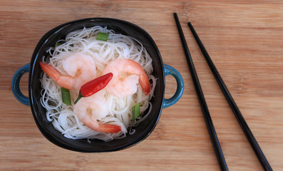 Rice vermicelli and shrimp in a bowl with chopsticks