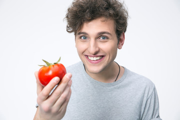 Smiling man holding tomato over gray background