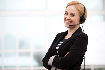Smiling call center female operator with headphones