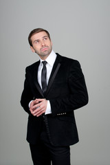 Businessman thinking and having ideas on a grey background with