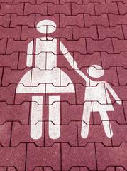 Mutter mit Kind Symbol in Rot weiß auf einem Parkplatz