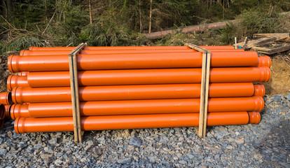 Orangene Rohre auf einer Baustelle gestappelt
