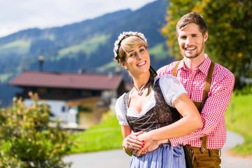 Paar in Tracht steht auf Alm in den Alpen