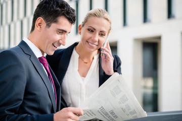 Mann und Frau arbeiten draußen mit Zeitung