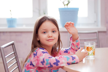 the girl sitting in the morning at the table and eat Breakfast