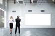 Geschäftsleute vor leerer Leinwand in großer Halle