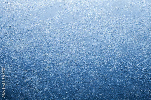 Thin ice layer of frozen river water - 79694727