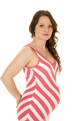 pregnant woman standing looking in a red and white dress