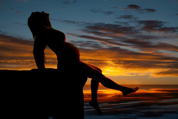 silhouette of a pregnant woman sitting back in the sunset