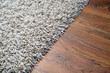 Leinwanddruck Bild - White shaggy carpet on brown wooden floor