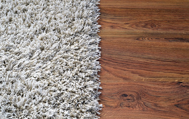 Two part split image of white shaggy carpet and wooden floor