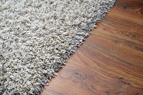 Leinwanddruck Bild White shaggy carpet on brown wooden floor