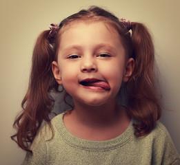 Funny kid girl showing tongue. Cool child joke. Vintage