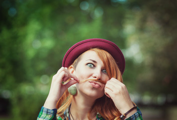 Hipster redhead woman making a moustache with her hair