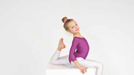 Pretty sporty slim girl sitting, doing split and stretching
