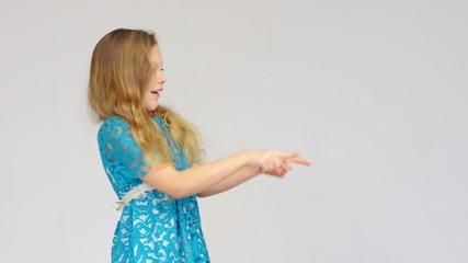 Happy girl in blue dress showing copy space between hands