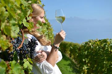 Girl tasting white wine among vineyards. Lavaux, Switzerland