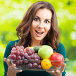 Happy woman with plate of fruits, outdoor