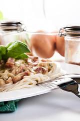 Spaghetti carbonara with bacon and basil