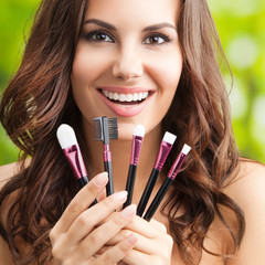 Cheerful smiling woman with make up tools, outdoor