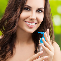Portrait of smiling woman with body lotion, outdoors