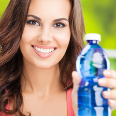Portrait of young smiling woman with bottle of water