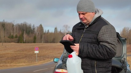 Man with tablet PC and empty can waiting for help near car