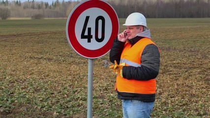 Worker talking on the cell phone near road sign