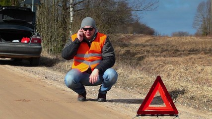 Man talking on the cell phone near warning triangle